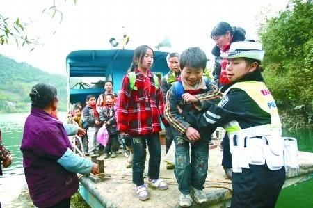 12月9日,武隆县石桥乡,民警邹芙容将孩子们抱下渡船。 记者 龙在全 摄