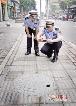 城管监督员正在使用手机进行现场采集。本报记者李文彬摄