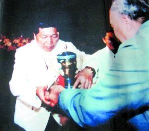 """1983年,李跃华(左)接受大赛颁发的""""最佳厨师奖杯""""。(翻拍)"""
