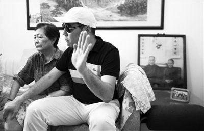 冰心之孙吴山和母亲陈凌霞接受采访,其身后摆放着冰心夫妇照片