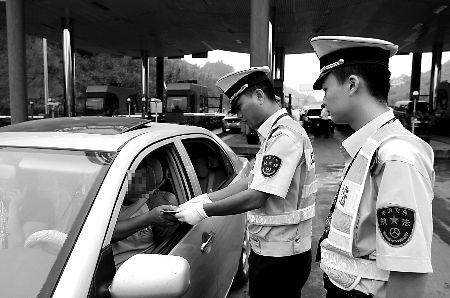 昨日,渝邻高速路草坝场收费站,执法人员在查看过往车辆的证件