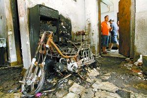 昨日弹子石盘龙花园小区五栋三单元4-1内一片狼藉,屋内的助力车也被烧毁。重庆晨报记者 王海 摄
