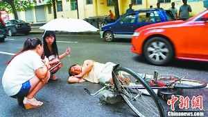 重师美女西安为摔伤老人撑雨伞