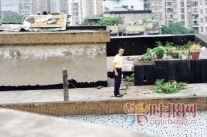 男子在居民楼顶对围观群众责骂