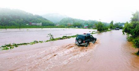昨日,铜梁县永嘉镇圣水村刘家沟,汽车在被洪水淹没的道路上行驶。