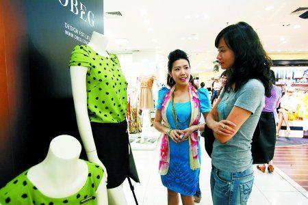 昨日,解放碑,陪逛员王冬英(左)在陪客户买衣服。
