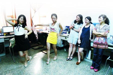 小施(左一)在办公室内练习爵士舞,不少同事围观