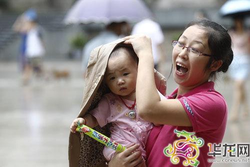 下雨啦!母亲紧忙为幼小孩子遮挡风雨