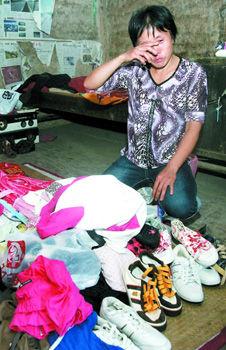 昨日,綦江区中锋镇板桥村,正在整理孩子们遗物的冉启芬不停地抹着眼泪。 记者 张永波 摄