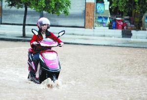 市民骑摩托小心翼翼驶过积水。