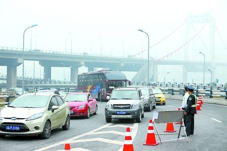 昨日,鹅公岩大桥引桥上通往谢家湾方向的匝道被封闭,协勤正引导车辆驶向南岸方向。