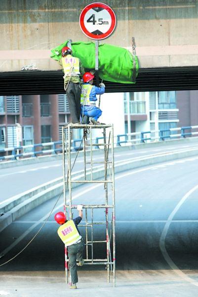 """昨日中午,工人正在处理鹅公岩大桥的""""受伤""""部位。"""