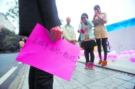 """昨日,西南大学,李乐拿着写有""""光棍节我们一起过""""的纸牌。"""