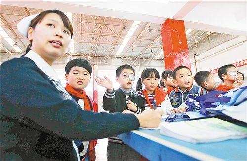 11月15日,在北部新区星光学校里,医务人员为小朋友做视力检测。