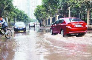 昨日,鲁能星城九街区B区门口,水管爆裂致路面大量积水,车辆缓慢通行。 本组图/重庆晨报见习记者 苑铁力 摄