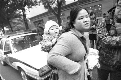 """""""8·10""""重庆持枪劫案中死者廖德应的妻子,独自背着不到8个月的孩子准备旁听,因孩子太小,未能进入法庭。张贵英庭上多次翻供。"""