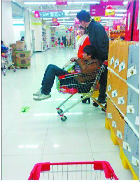 """两男子轮流坐在购物推车内 拍客""""航向标""""摄于大足区某超市"""