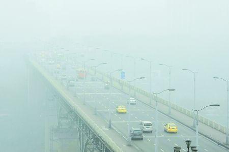 昨日,雾霾中的嘉陵江大桥。