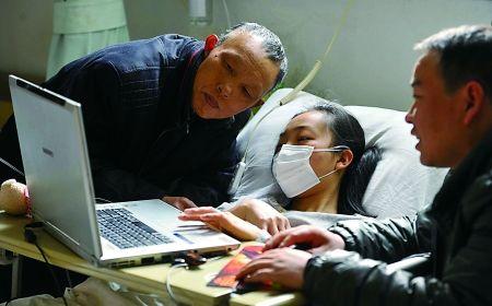 昨日,西南医院,朱飞燕和父亲(左一)正用网友带来的电脑查看网友们的祝福。 记者 张路桥 摄