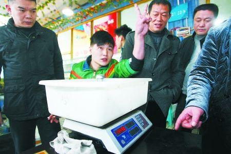 昨日,三亚湾水产市场,一男子在电子秤前摆起了POSE。 记者 吴珊 摄