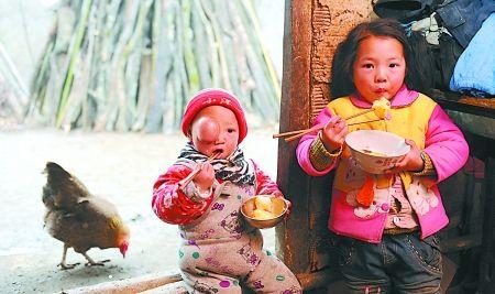小冰冰和姐姐钟燕坐在门槛上吃午饭,碗里的洋芋就是她们的主食。