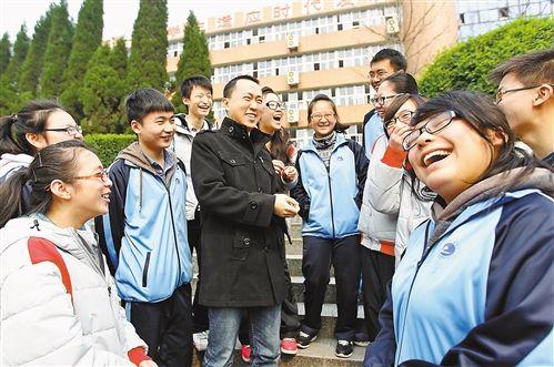 26日,在市实验中学(原巴县中学)校园,曾就读于该校的何易(中)与学弟学妹们一起交流学习经验。 记者 卢越 摄