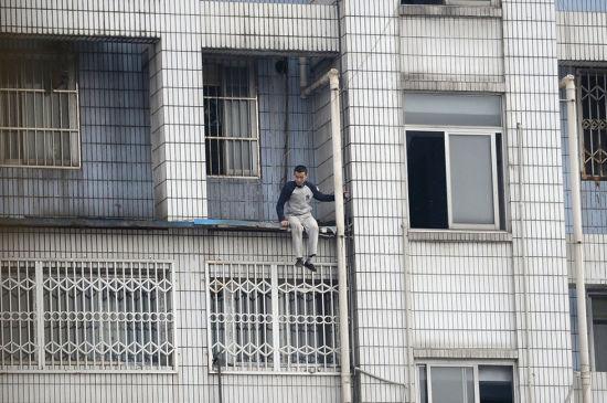 2013年3月20日,四川省成都市,蹲在阳台雨棚上的男子。