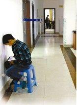 男孩孤单地坐在走廊上,头顶着墙,目不转睛地盯着iPad。