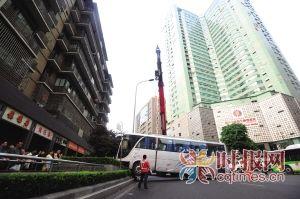 上清寺转盘国宾医院处,吊车正在吊起冲上花台的大巴车