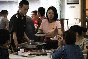 大学生在给客人端菜