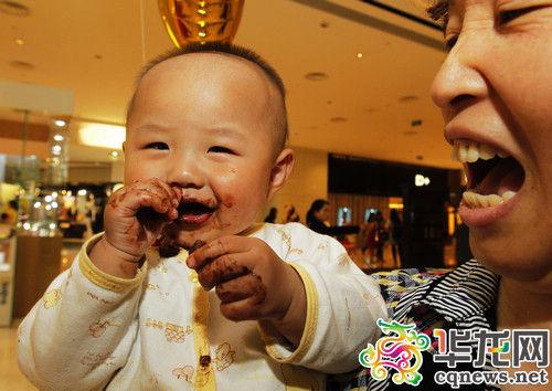 一名贪吃的小孩,脸上手上都糊满了巧克力。 记者 罗嘉 摄