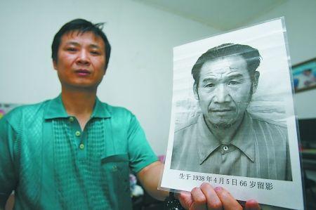 余家祥拿着父亲的照片,盼望能早日与离别30年的母亲团聚