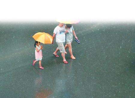 昨日,沙坪坝区,市民打着伞走在路上。 记者 张路桥 实习生 程雯丽 摄