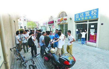 沙坪坝区大学城熙街,驾校学员在等待驾校解决他们反映的问题。