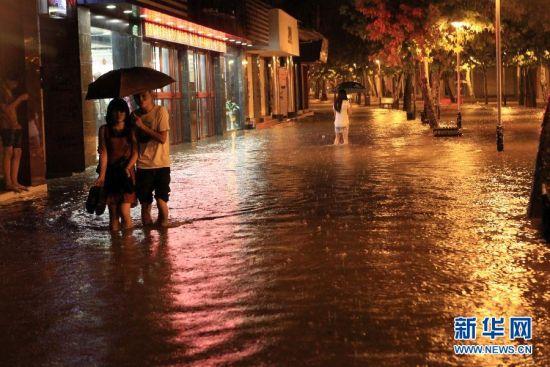 6月30日晚,在重庆市大足区一步行街,市民从积水路面走过。