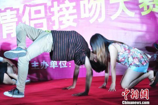 在接吻大赛现场,一小伙倒翻身手脚支撑仰头接受女友亲吻