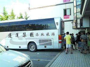 11日下午5点30分,游客们聚在大巴车前。