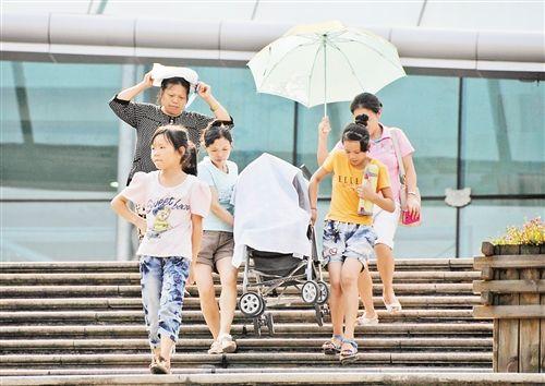8月13日,渝中区人民广场,几位市民用毛巾为婴儿车里的孩子遮挡阳光。