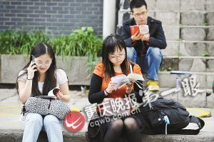 考生在考场外席地而坐,抓紧时间看书。