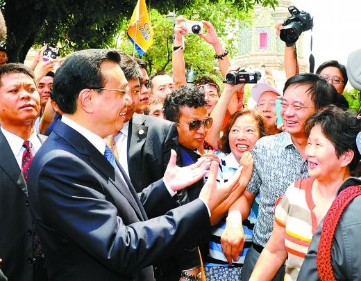 12日,李克强在曼谷与中国游客互动交流,了解中泰两国旅游交往情况。