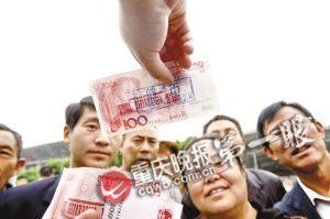 银行人员教群众识别假币(资料图片)