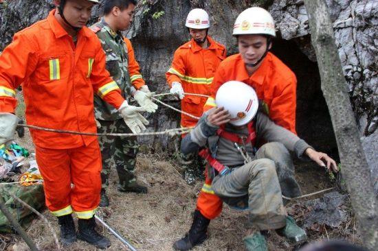 11月14日,广西都安县,一名男子在掉进8米深的洞穴中被困9天后被救出。在被困的这8天里他一直以吃垃圾维持生命。图为营救现场。