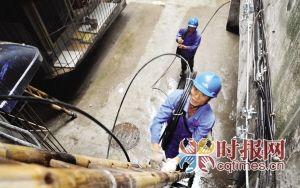 渝中区大坪,电力工人搬来新的电缆线更换居民旧的电缆线