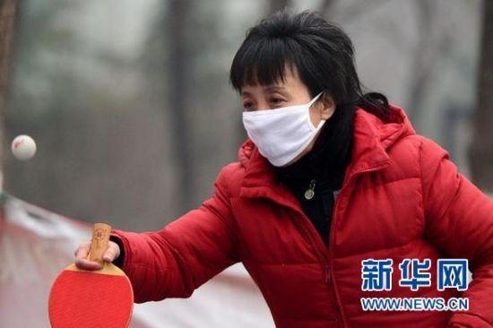 资料图片:1月6日,在济南市马鞍山健身广场,一名市民戴着口罩打乒乓球。当日,山东省气象局继续发布霾黄色预警信号,菏泽、济宁、济南等9市的中度霾天气仍将持续。