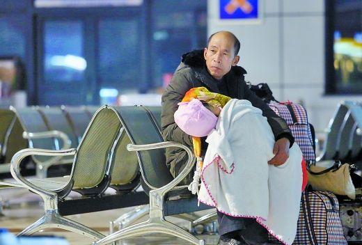 17日凌晨1点,龙头寺汽车站,一位父亲抱着孩子等待天亮。