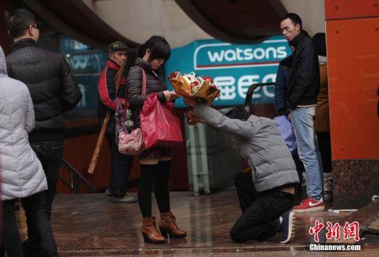 """2月10日,重庆沙坪坝步行街上一年轻小伙单膝下跪献花给一女士,女士迟迟不接。路过市民扎堆齐喊""""嫁给他"""",最后女士才接过该小伙子的鲜花,两人相依离去。图为一年轻小伙单膝下跪献花给女士。"""