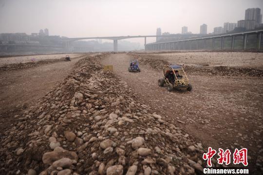 图为重庆市民正在干枯的河床上开卡丁车比赛。 陈超 摄