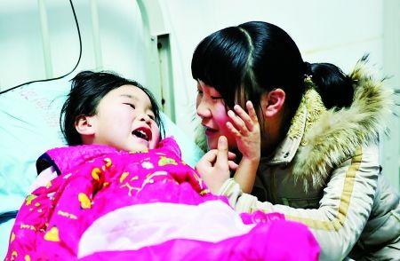 昨日,儿童医院,李开琴在病床前陪妹妹李娟聊天。