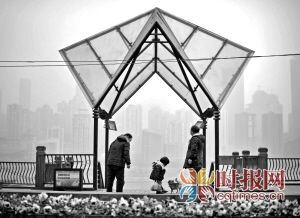 民在南滨路玩耍,不远处朦胧的城市轮廓,就是一江之隔的渝中半岛
