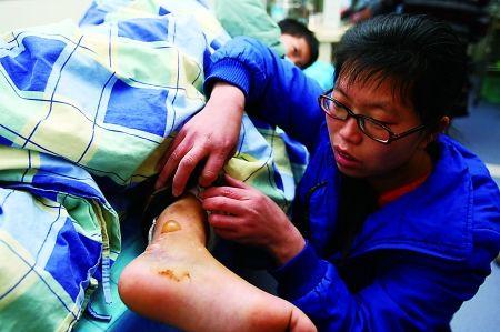 昨日,大坪,小靳的妈妈钟女士撩开被子露出儿子肿胀的脚。